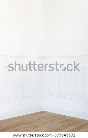 Empty white room corner with parquet floor and wood trimmed wall - stock photo