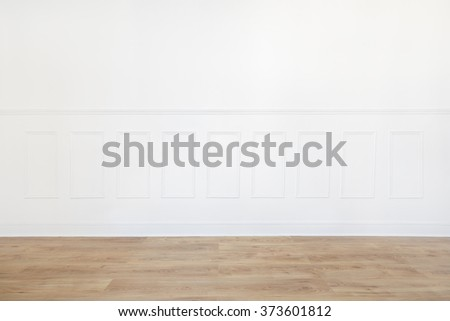 Empty white room with wooden floor and wood trimmed wall - stock photo
