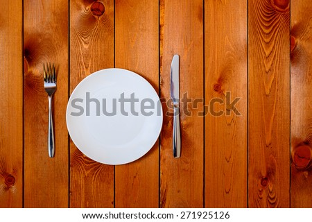 Empty white round plate with antique knife and fork on wooden background. Top View with text space. - stock photo