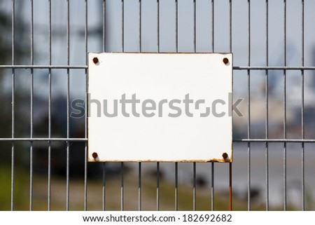 Empty white sign on worn industrial fence offers copy space. - stock photo
