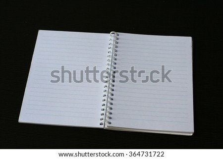 Empty white spiral lined notepad on black wooden table prepared for new ideas and messages - stock photo