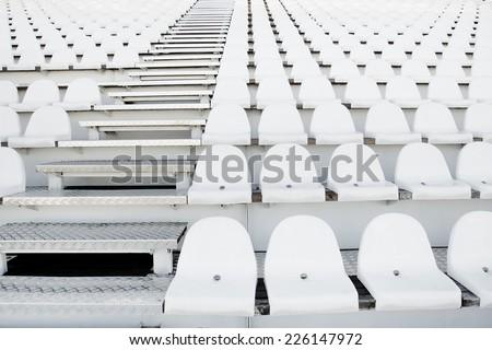 Empty white stadium seats on grandstandof the football stadium. - stock photo