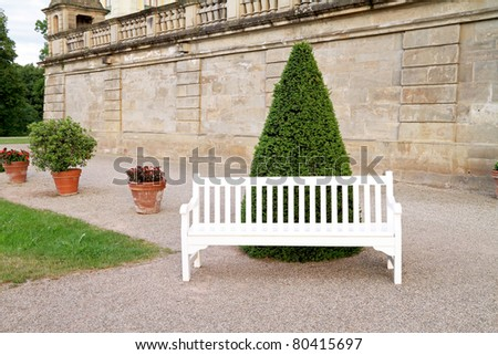 Empty white wooden bench in yard