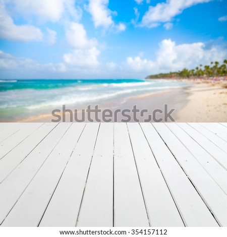 Empty white wooden pier perspective with blurred beach landscape on a background - stock photo