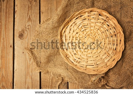 Empty wicker basket on sackcloth on wooden table background. View from above - stock photo