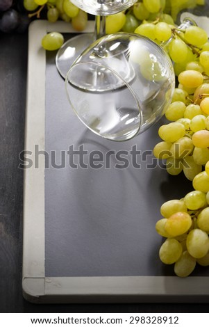 empty wine glass and grapes on a blackboard, vertical - stock photo