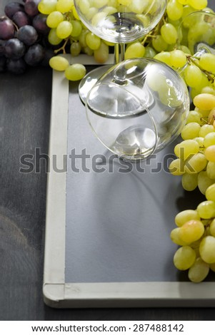 empty wine glass and grapes on a blackboard, vertical, top view - stock photo