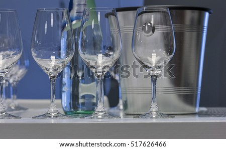 Empty wine glasses closeup in a row and ice bucket, focus on foreground