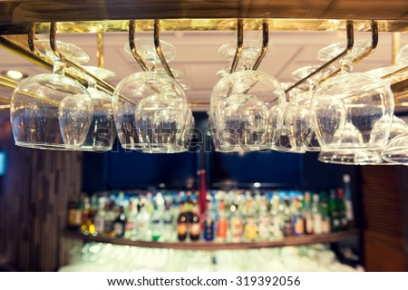 Empty wine glasses on the bar rack, Vintage filter. - stock photo