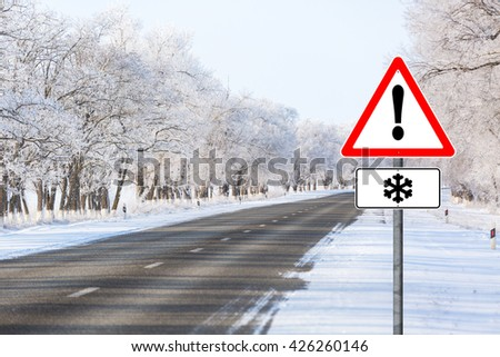 Empty winter road, road sign warning snowfall, Exclamation point, a lot of snow, snowfall, frost on branches. clean road asphalt - stock photo