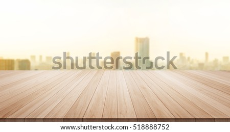 Empty wood table top on panoramic modern cityscape building under sunrise and morning blue bright sky background for display or montage product