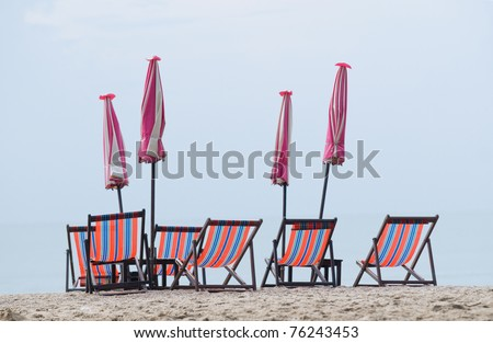 Empty, wooden beach chairs and folded parasols at the beach on a cloudy morning. - stock photo