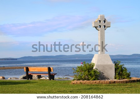 Empty wooden bench by a celtic cross memorial with a view of the ocean of Bay of Fundy in St. Andrew by the Sea, New Brunswick, Maritimes, Canada - stock photo