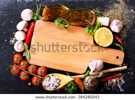 empty wooden board  with various products for cooking on dark board