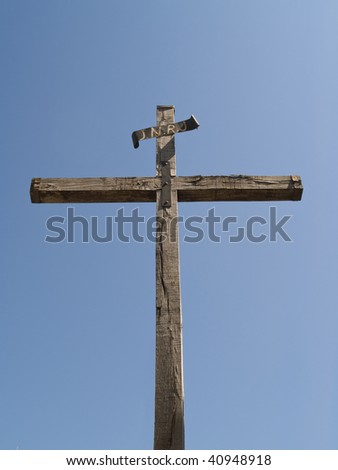 empty wooden cross against blue sky. - stock photo