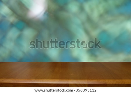 Empty wooden deck table over blur green light abstract background. Ready for luxury product display montage.