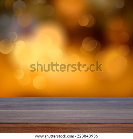 Empty wooden deck table with a sparkling bokeh of party lights in the background - stock photo