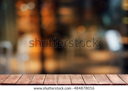 Empty wooden deck table with cafeteria, coffee shop or pub, soft focus background. Ready for product display montage.