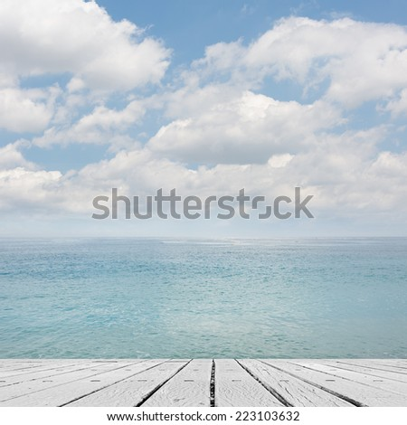 Empty wooden deck table with copyspace under sunny cloudy sky in the beach, focus on the wooden ground. - stock photo