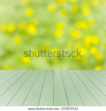 Empty wooden deck table with green and yellow soft focus background. Ready for product display montage. - stock photo
