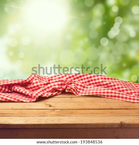 Empty wooden deck table with tablecloth over green bokeh background - stock photo