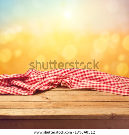 Empty wooden deck table with tablecloth sunset bokeh background - stock photo