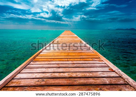Empty Wooden Dock Over Tropical Blue Water - stock photo
