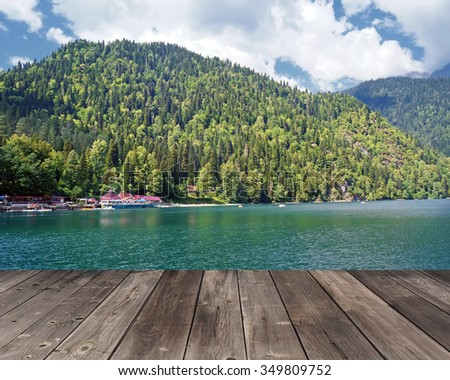 Empty wooden flooring against the lake in mountains. View of Ritsa lake in mountains in Abkhazia in a summer sunny day. - stock photo