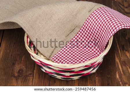Empty wooden fruit or bread basket on an old vintage planked wood table with burlap sack cloth - stock photo