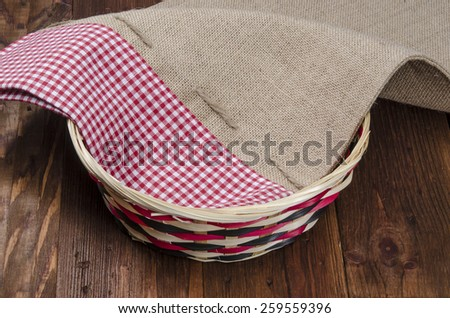 Empty wooden fruit or bread basket on an old vintage planked wood table with burlap sack cloth. Rural or rustic kitchen still life. - stock photo