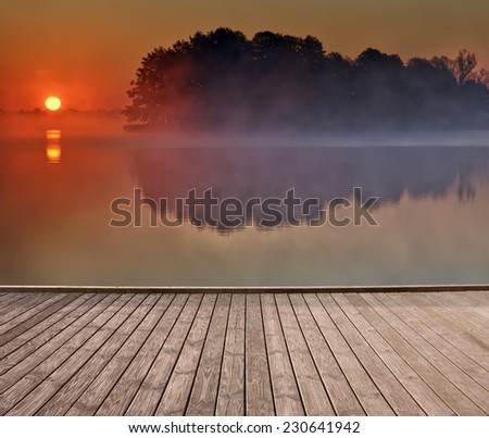 Empty wooden jetty on the lake shore with small island on calm foggy lake water surface in the background just after sunrise - stock photo