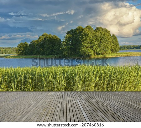 Empty wooden jetty on the lake shore with small uninhabited island in the background - stock photo
