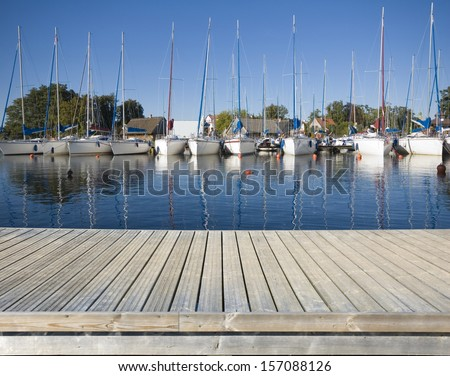 Empty wooden jetty on the lake shore with yachts moored in marina - stock photo