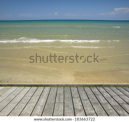 Empty wooden jetty with sandy beach in the background - stock photo