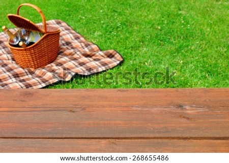 Empty Wooden Picnic Tabletop Close-up. Picnic Basket and Blanket On The Summer Lawn In The Background. - stock photo
