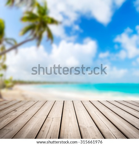 Empty wooden pier background over blurred tropical beach coastal landscape with palm tree, cloudy sky and bright sea water