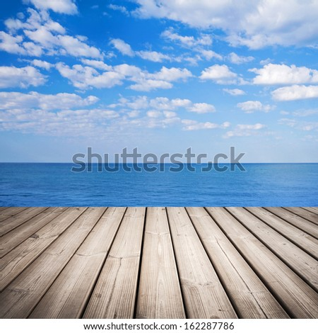Empty wooden pier with sea and cloudy sky on background - stock photo