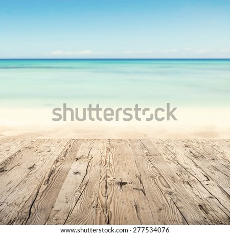 Empty wooden pier with view on sandy beach. Free space for text or product placement - stock photo