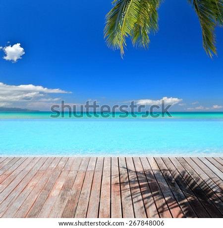 Empty wooden platform with tropical beach infinity swimming pool -- Tropical vacation and travel concept