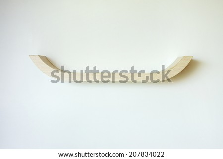 empty wooden shelf on white wall - stock photo