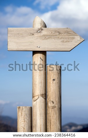 Empty wooden sign on blue sky background.