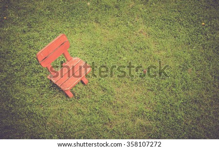 Empty wooden stool on green grass field - stock photo