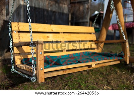 Empty wooden swing in the backyard with selective focus - stock photo