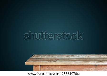 Empty wooden table against a blue wall. A blank space for.