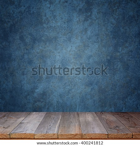 Empty wooden table against a blue wall. A template, a place for.  Blue grunge texture.