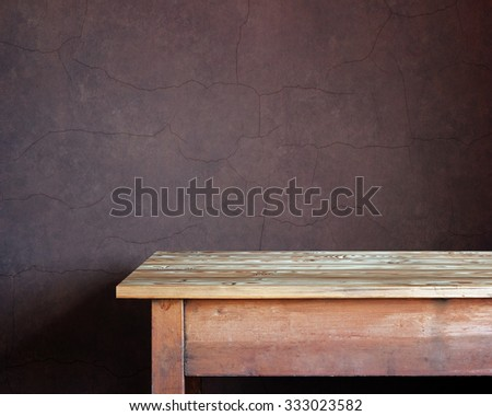 Empty wooden table against a wall with cracks. A blank space for.