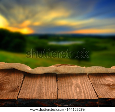 Empty wooden table and beautiful summer field  in background. Great for product display montages - stock photo