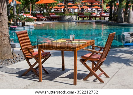 Empty wooden table and chairs in cafe next to the swimming pool, Thailand - stock photo