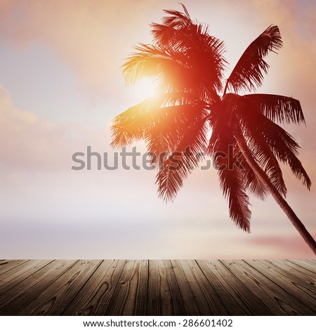 Empty wooden table and coconut palm tree over the sunset beach. Tropical banner background. - stock photo