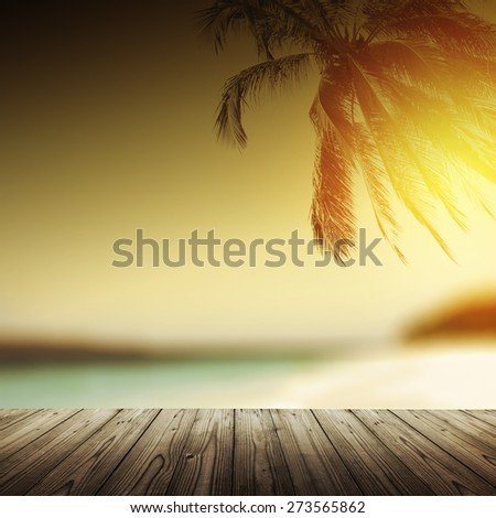 Empty wooden table and tropical beach at sunset with coconut palm silhouette. Vintage effect.  - stock photo